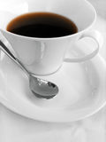 Coffee cup and spoon. An image of a wide brim white porcelain coffee cup on a matching saucer.  With a silver spoon beside.  Black coffee in cup.  Simple and Stock Photography