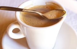 Coffee cup with spoon above the edge Royalty Free Stock Images