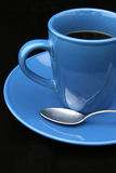 Coffee Cup and Spoon on Black. A bright blue cup of coffee with a spoon, against a black background stock images