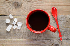 Coffee cup, spoon and rock sugar on wooden table Royalty Free Stock Photo