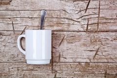 Coffee cup and spoon. On rustic wooden background Royalty Free Stock Photo