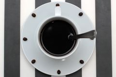 Coffee cup with spoon on saucer and coffee beans against white background forming clock dial. View from above. Coffee as symbol of. Morning energy and Stock Photos