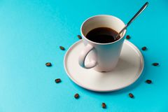 Coffee cup with spoon on saucer and coffee beans against blue background forming clock dial. Coffee as symbol of morning energy stock images