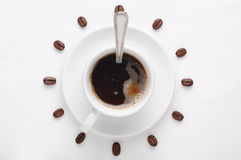 Coffee cup with spoon on saucer and coffee beans against white background forming clock dial viewed from top Stock Photo