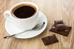 Coffee in cup, spoon on saucer and pieces of chocolate Stock Images