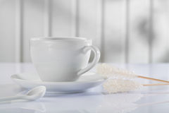 Coffee cup with spoon and sugar stickon white table Royalty Free Stock Image