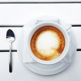 Coffee cup and spoon on white wooden table Stock Images