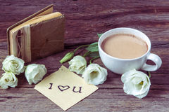 Coffee cup with spring flower lisianthus and notes I love you on. Wooden table Stock Photography
