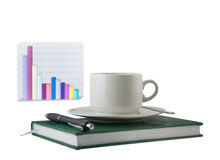 Coffee cup, standing on the green organizer. Coffee cup, standing on the green personal organizer, on a back background - financial diagram . Focus at the pen royalty free stock image