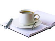 Coffee cup, standing on the daily organizer. Stock Photo