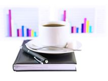 Coffee cup, standing on the organizer. Isolated. Coffee cup, standing on the personal organizer, on a back background-financial diagrams . Isolated Stock Image