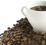 Coffee in a cup stands on grains of coffee Royalty Free Stock Photography