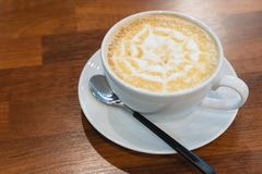 Coffee cup with star shape art foam on wood table background on table top at cafe stock photography