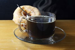 Coffee cup with steam and donut closeup Royalty Free Stock Photos
