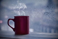 Coffee cup. Steaming coffee cup on a rainy day window background Royalty Free Stock Photography