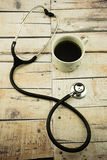 Coffee cup and stethoscope on wooden background. Stock Images