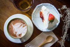 Coffee cup and strawberry cake in coffee shop  with wood backgro Royalty Free Stock Photography