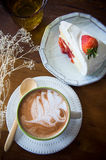 Coffee cup and strawberry cake in coffee shop  with wood backgro Royalty Free Stock Photo