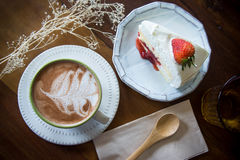 Coffee cup and strawberry cake in coffee shop with wood backgro. Und vintage style stock photography