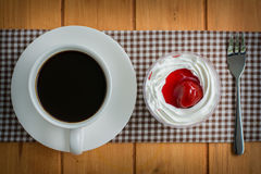 Coffee cup with strawberry cake on wooden table Stock Photo