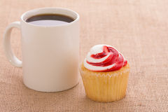 Coffee cup with a strawberry flavored cupcake Stock Photo