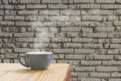 Coffee cup with stream of vapour against white brick wall background. royalty free stock images