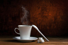 Coffee cup and sugar. White ceramic cup with hot coffee with smoke on saucer, ceramic spoon and lumps sugar on wooden table on dark brown  alight background Stock Photography