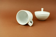 Coffee cup and sugar bowl laying on brown background.  Royalty Free Stock Photography