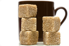 Coffee cup with sugar cubes. Coffee cup with a pile of brown sugar cubes Stock Photos