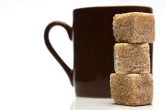 Coffee cup with sugar cubes. Coffee cup with a pile of brown sugar cubes Royalty Free Stock Images