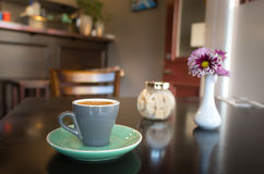 Coffee cup, sugar and a flower. Simple cup of espresso with cubes sugar and a flower on a wooden table Royalty Free Stock Photo