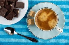 Coffee in cup, sugar on saucer, plate with pieces of chocolate, spoon on napkin. Top view. Coffee espresso in blue cup, sugar cubes on saucer, plate with pieces stock image