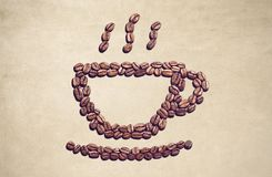 Coffee cup symbol made out of coffee beans. Many coffee beans forming a coffee cup symbol on a brownish background Royalty Free Stock Images