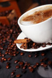 Coffee cup on the table with coffee beans around Stock Photo