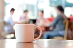 Coffee cup on the table in coffee shop. Coffee cup on the table with people in coffee shop as blur background Royalty Free Stock Photography