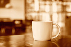 Coffee cup on the table in coffee shop - sepia tone Royalty Free Stock Image