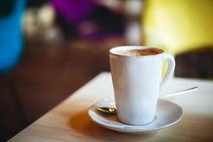 Coffee cup on the table in empty cafe. Blurred background, selective focus, space for text stock photo