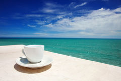 A coffee cup on table over sea background. A cup of coffee on table with beautiful sea background Stock Photography