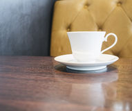 Coffee cup on table in restaurant cafe with sofa background Stock Image