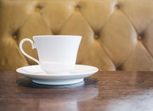 Coffee cup on table in restaurant cafe with sofa background Royalty Free Stock Image