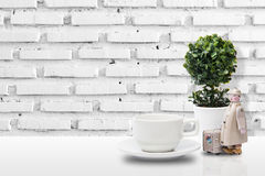 Coffee cup on table. With wall brick and tree pot stock image