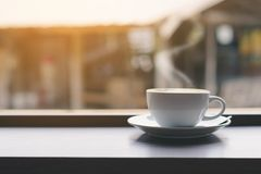 Coffee cup on the table and window stock photography