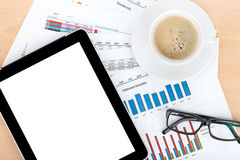 Coffee cup, tablet over papers with numbers and charts Stock Photo