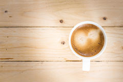 Coffee cup taken in top view on wooden table Royalty Free Stock Images