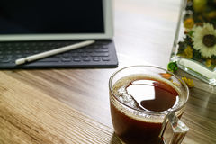 Coffee cup or tea and Digital table dock smart keyboard,vase flo. Wer herbs,stylus pen on wooden table,filter effect Royalty Free Stock Photo