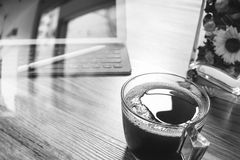 Coffee cup or tea and Digital table dock smart keyboard,vase flo. Wer herbs,stylus pen on wooden table,filter effect,black white Stock Photo