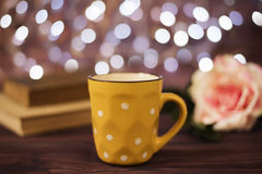 Coffee cup, tea, old books and rose on wood table in cafe with bokeh light background. Leisure lifestyle concept. stock photos
