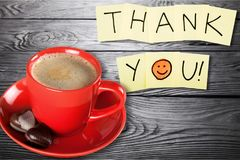 Coffee cup and thank you note   on wooden. Cup coffee note thank you background shape closeup Stock Image