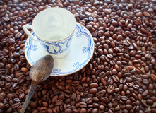 Coffee cup from thin porcelain against the background   grains Royalty Free Stock Photography