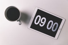 Coffee cup with time display on digital clock on tablet computer. Morning coffee with time on digital clock Stock Photo